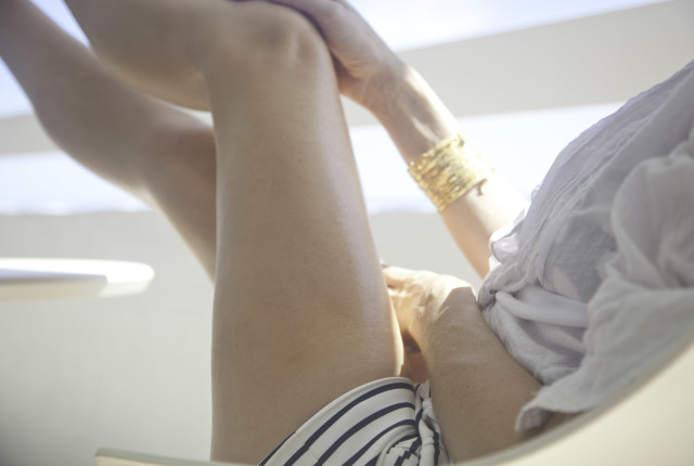 a woman's beautiful legs relaxing on a condo balcony by the ocean